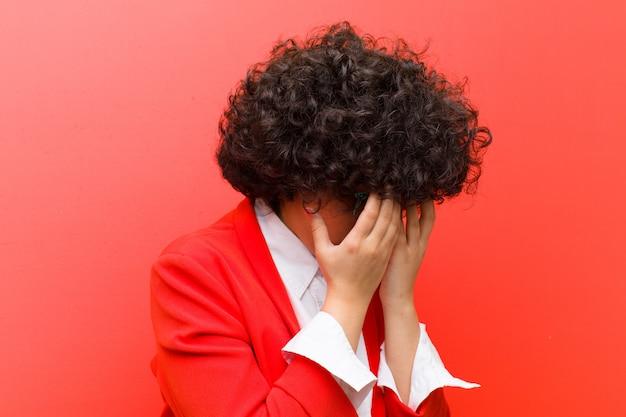 Молодая афро женщина закрыла глаза руками с грустным, разочарованным взглядом отчаяния, плача, вид сбоку