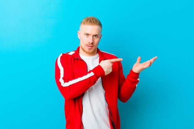 Молодой блондин человек носить спортивную одежду, весело улыбаясь и указывая, чтобы скопировать пространство на ладони на стороне, показывая или рекламируя объект