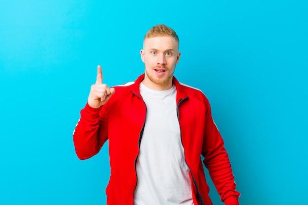 アイデアを実現した後、幸せで興奮した天才のように感じ、元気に指を上げたスポーツウェアを着た若い金髪の男、ユーレカ!