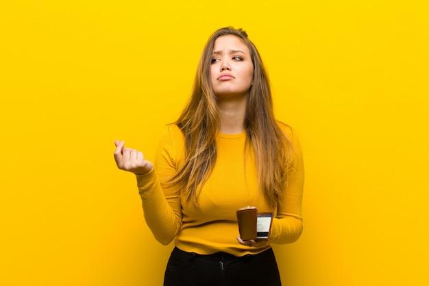 オレンジ色の壁に対して若いきれいな女性お金の概念