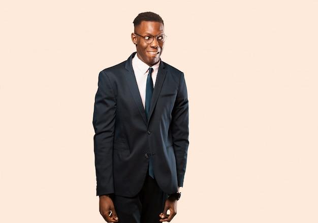 Афро-американский бизнесмен, выглядящий взволнованным, подчеркнутым, взволнованным и напуганным, паникующим и стискивающим зубы на бежевой стене