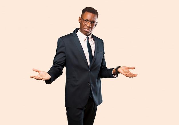 Афро-американский бизнесмен выглядит озадаченным, смущенным и подчеркнутым, размышляя о разных вариантах, чувствуя себя неуверенно на фоне бежевой стены