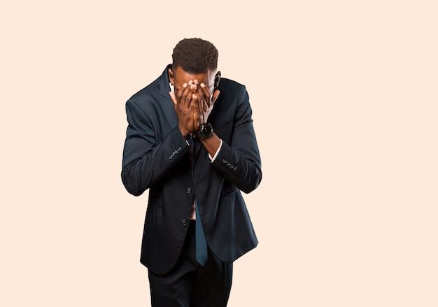 Афро-американский бизнесмен чувствует грусть, разочарование, нервозность и депрессию, закрывая лицо обеими руками, плача против бежевой стены