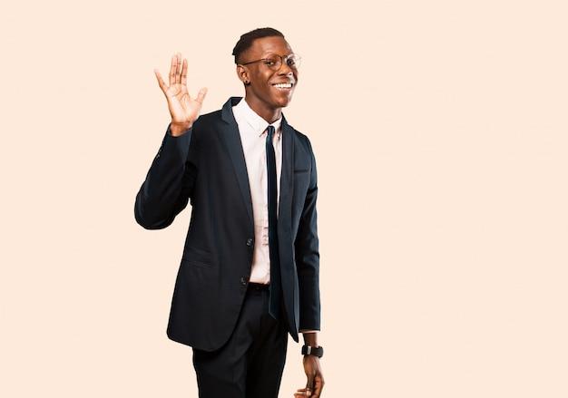 アフリカ系アメリカ人のビジネスマンが笑顔で幸せに、元気に、手を振って、歓迎と挨拶、またはベージュの壁に別れを告げる