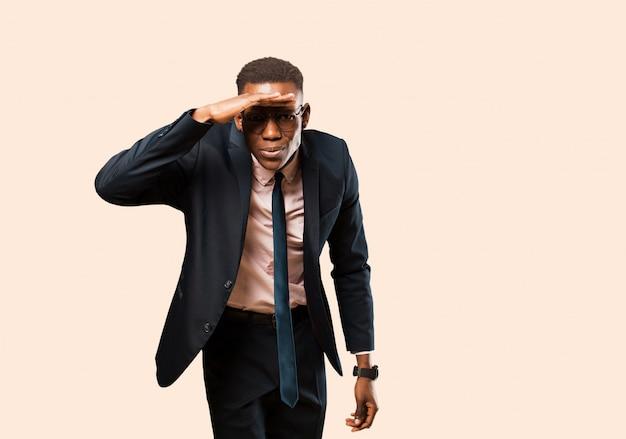 額に手をかざすと遠くを見て、ベージュの壁を見て、または探して、戸惑ってびっくりして見えるアフリカ系アメリカ人のビジネスマン