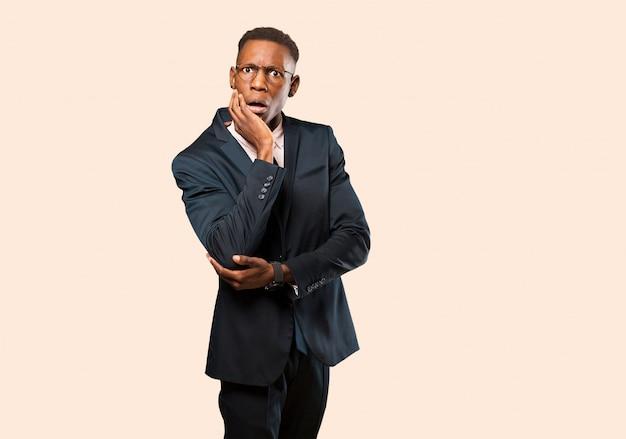 ショックと不信に口を開けたアフリカ系アメリカ人のビジネスマン、頬と腕を交差させた手で、ベージュの壁に戸惑い、驚いた