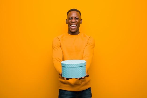 贈り物でオレンジ色の壁に若いアフリカ系アメリカ人の黒人男性