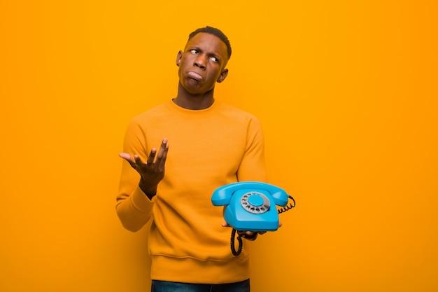 ビンテージ電話でオレンジ色の壁に若いアフリカ系アメリカ人の黒人男性