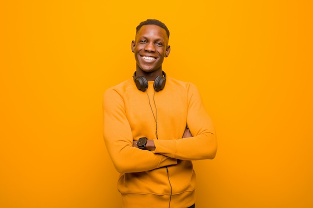 ヘッドフォンでオレンジ色の壁に若いアフリカ系アメリカ人の黒人男性