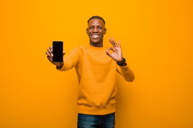 Молодой афроамериканец черный человек против оранжевой стены с умным телефоном