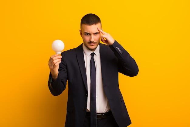 Молодой красивый бизнесмен на плоском фоне с лампочкой