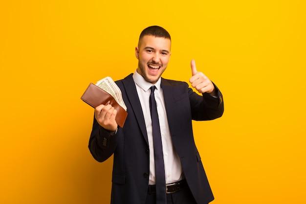 フラットバックグラウンドお金概念に対して若いハンサムな実業家