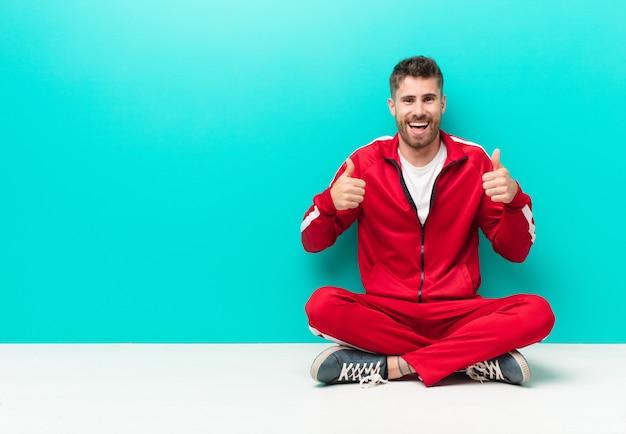 Молодой человек ручной работы, широко улыбаясь, выглядит счастливым, позитивным, уверенным и успешным, с двумя большими пальцами к плоской цветной стене