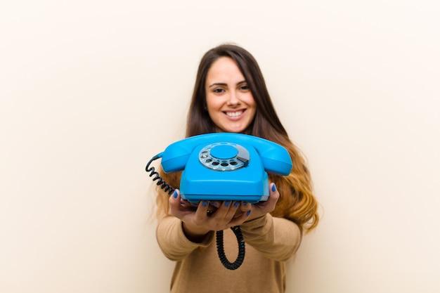 青いビンテージ電話で若いきれいな女性