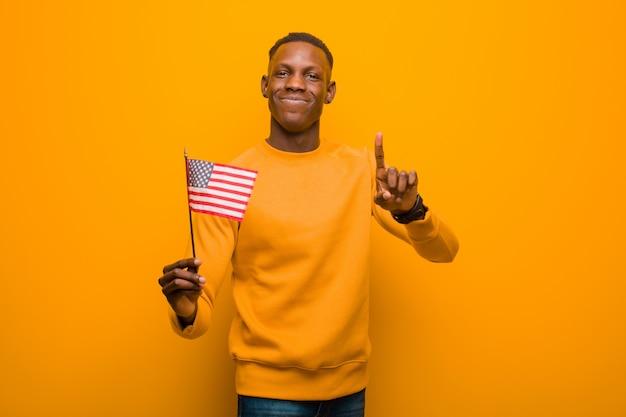 アメリカの国旗を保持しているオレンジ色の壁に対して若いアフリカ系アメリカ人の黒人男性