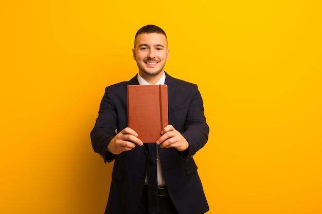 日記の本で平らな壁に若いハンサムな実業家
