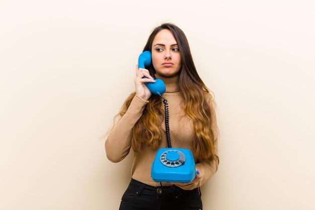 Молодая милая женщина с голубым винтажным телефоном