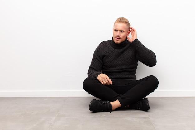 Молодой блондин человек выглядит серьезным и любопытным, слушая, пытаясь услышать секретный разговор или сплетни, подслушивая сидя на цементном полу