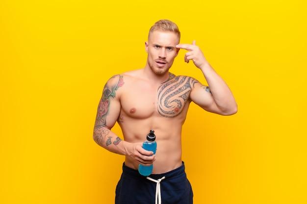 Молодой блондин сильный мужчина чувствуя себя смущенным и озадаченным, показывая, что вы безумны, сумасшедшие или сошли с ума с энергетическим напитком