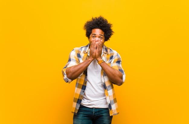 オレンジ色の壁の上の両手で幸せ、陽気、幸運、驚きのカバー口を探している若い男
