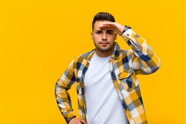 困惑してびっくりした若い男、額に手をかざすと遠くを見て、オレンジ色の壁を見たり検索したりする