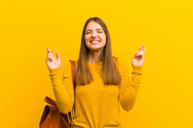 若いきれいな女性の笑みを浮かべて、両方の指を心配そうに交差、心配と希望またはオレンジ色の壁の幸運を願って