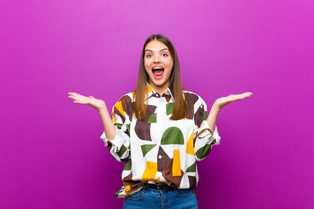 Молодая симпатичная женщина, выглядящая счастливой и взволнованной, потрясенная неожиданным сюрпризом, с открытыми руками рядом с лицом над фиолетовой стеной