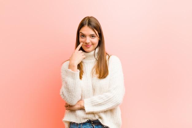 若いきれいな女性、あなたに目を光らせて、信頼していない、見て、ピンクの壁の上の警戒と警戒を維持