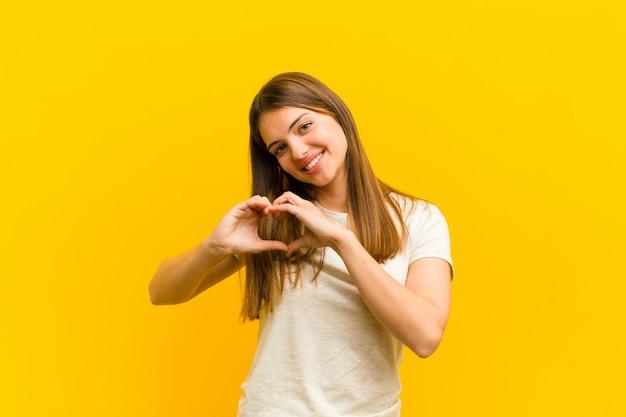 Молодая красивая женщина улыбается и чувствует себя счастливой, милой, романтичной и влюбленной, делая форму сердца обеими руками над оранжевой стеной