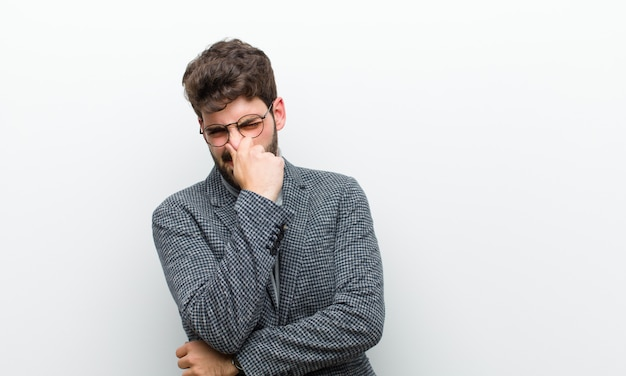 Молодой менеджер человек чувствует отвращение, держа нос, чтобы не пахнуть грязной и неприятной вонь над белой стеной