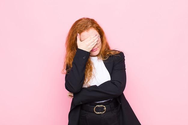 Молодая рыжеволосая женщина выглядит подчеркнуто, стыдно или расстроена, с головной болью, закрыв лицо рукой над розовой стеной