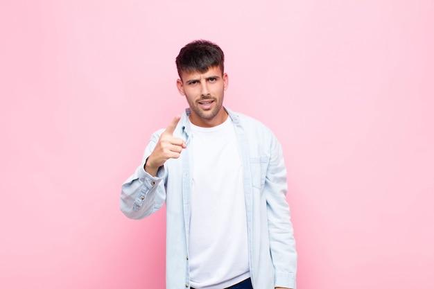 ピンクの壁の上の猛烈な、狂った上司のように見える怒っている積極的な表現で指している若いハンサムな男