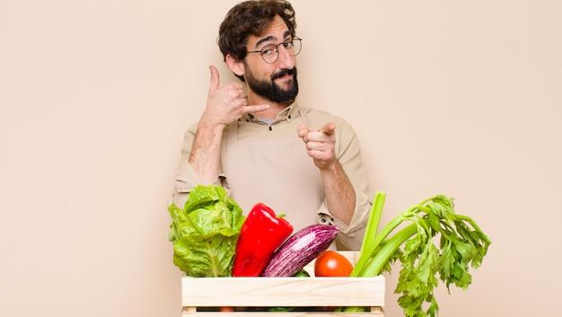 Зеленый продуктовый человек, весело улыбаясь и указывая во время звонка вам позже жест, разговаривает по телефону
