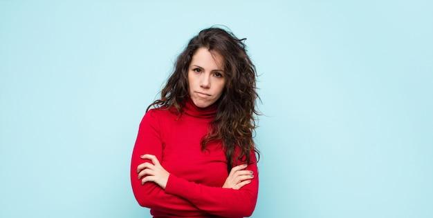 Молодая симпатичная женщина чувствует себя недовольной и разочарованной, выглядит серьезной, раздраженной и злой со скрещенными руками над синей стеной