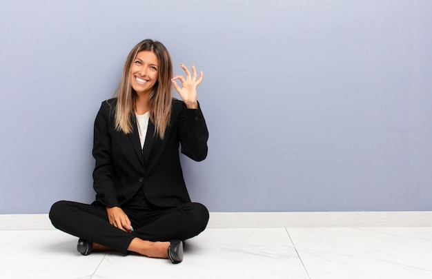 Молодая красивая женщина чувствует себя счастливым, расслабленным и довольным, показывая одобрение в порядке жестом, улыбаясь
