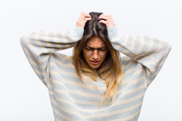 ストレスや欲求不満を感じ、手を頭に上げ、疲れ、不幸を感じ、白い壁に片頭痛を持つ若いきれいな女性