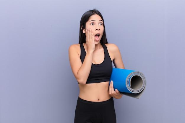 Молодая симпатичная женщина с ковриком для йоги над цементной стеной