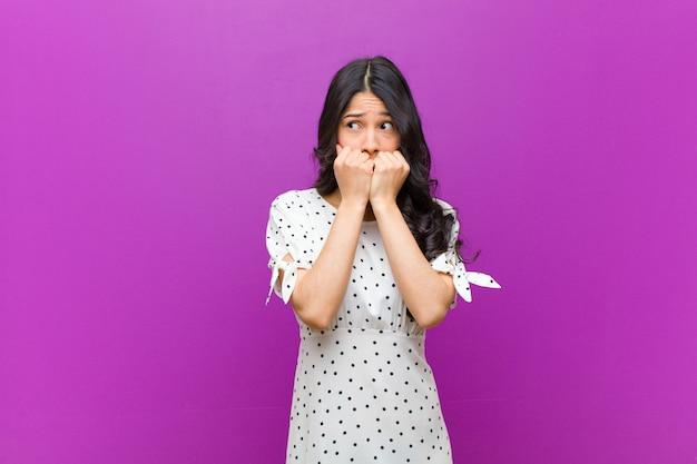 心配、不安、ストレス、恐れ、爪をかむと紫色の壁の外側を探している若いきれいな女性