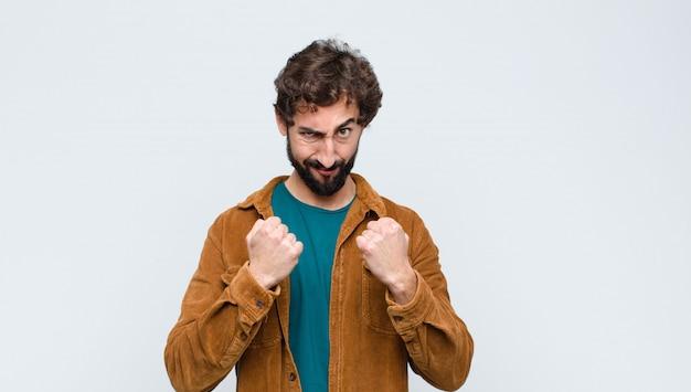 自信を持って、怒って、強くて攻撃的な若いハンサムな男、拳を壁の上のボクシングの位置で戦う準備ができて