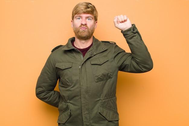 深刻な、強く、反抗的な感じ、拳を上げる、抗議または壁を越えて革命のために戦う若いブロンドの男