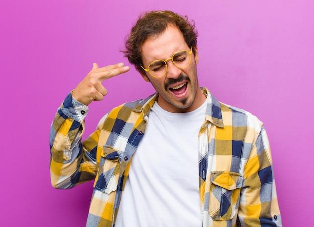 紫色の壁の上の頭を指している手で銃のサインを作る不幸とストレス、自殺ジェスチャーを探している若いハンサムな男