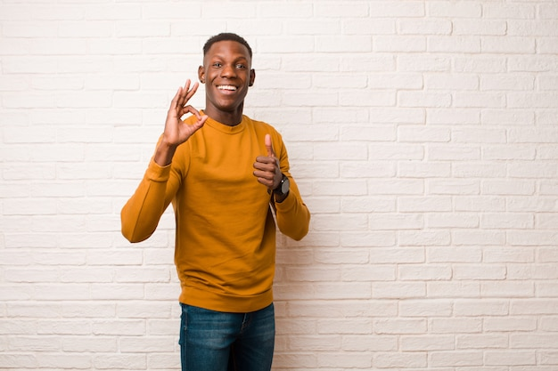 若いアフリカ系アメリカ人の黒人男性は幸せ、驚き、満足、驚きを感じ、大丈夫とジェスチャーを親指を示す、レンガの壁を越えて笑顔