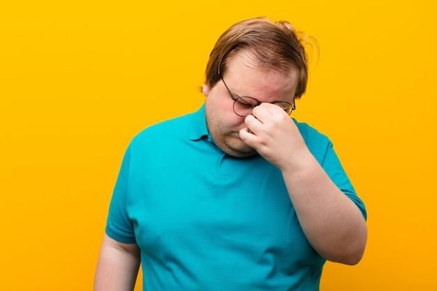 ストレス、不幸、欲求不満、額に触れるとオレンジ色の壁の上の激しい頭痛の片頭痛に苦しんでいる若い大きなサイズの男