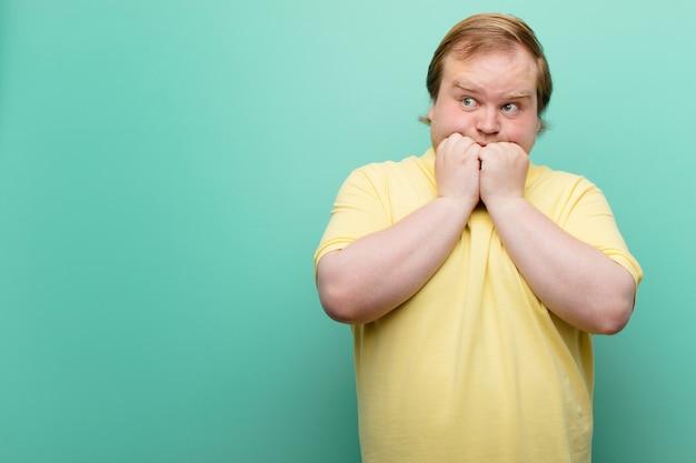 心配、不安、ストレス、恐れ、爪をかむと横に探している若い大きなサイズの男