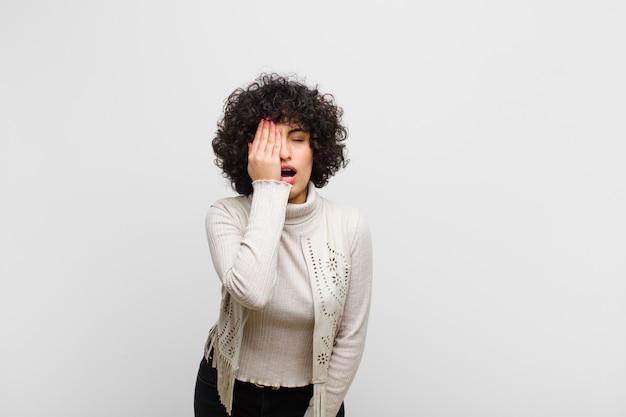 Молодая симпатичная женщина выглядит сонной, скучающей и зевая, с головной болью и одной рукой, закрывающей половину лица
