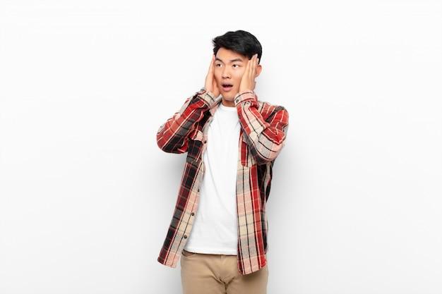 幸せ、興奮、驚きを感じて、色の壁を越えて顔に両手で側を見て若いアジア人