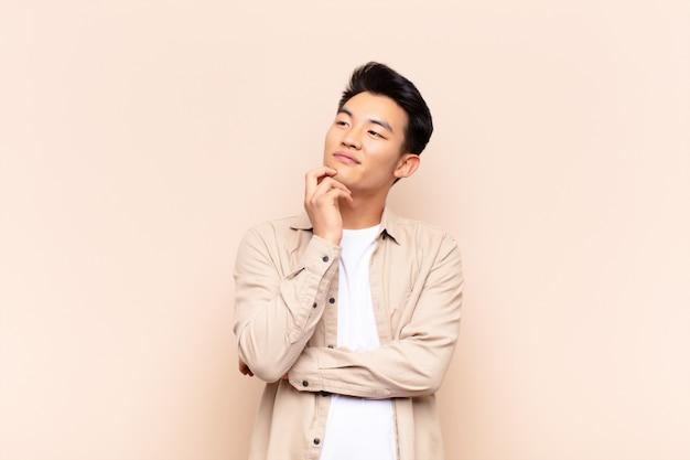 Молодой азиатский человек улыбается счастливо и мечтать или сомневаться, глядя в сторону над цветной стеной