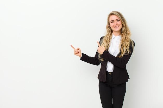 幸せな笑顔と白い壁の上のコピースペースでオブジェクトを示す両方の手で側と上を指している若いブロンドの女性