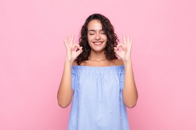 集中して瞑想を見て、満足とリラックスを感じて、思考またはピンクの壁を越えて選択をする若いきれいな女性