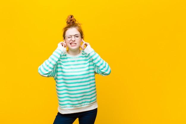 Молодая рыжеволосая женщина выглядит злой, напряженной и раздраженной, прикрывая оба уха оглушительным шумом, звуком или громкой музыкой над оранжевой стеной